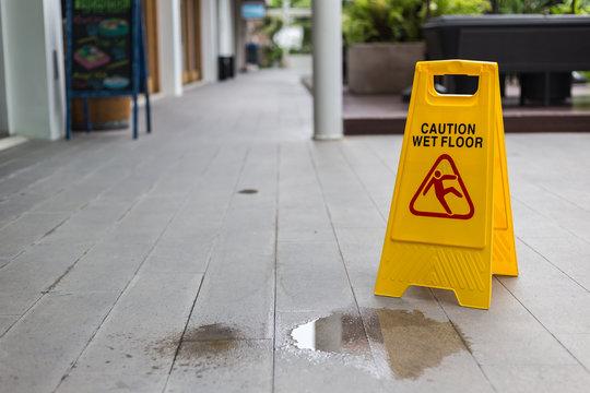 Yellow wet floor warning sign on the floor in hotel