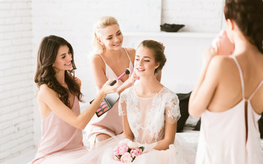 Cheerful bridesmaids preparing the young bride to the wedding ceremony