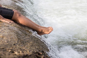 Woman sitting at waterfall