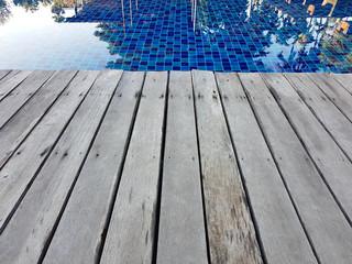 Close focus of edge of wood floor near swimming pool.