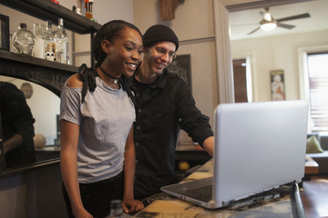 Smiling young couple using laptop while standing indoors