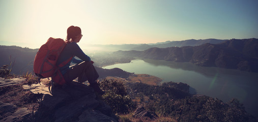successful woman backpacker enjoy the view at mountain peak