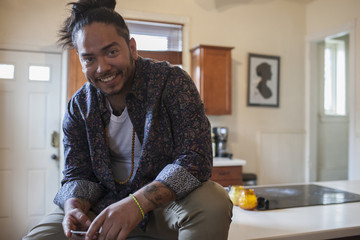 Portrait of smiling young man sitting on kitchen countertop
