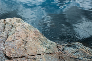 Large pick rock with deep blue water in background