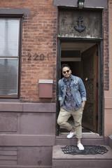 A young man on a doorstep.