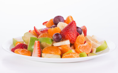 Colorful fruit salad heaped on a white plate