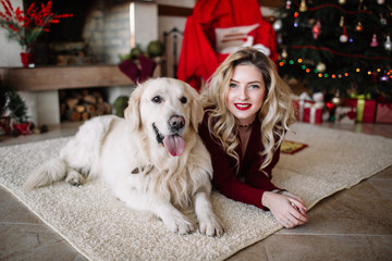 Cute young woman and her dog at Christmas sitting together on the floor in front of the decorated tree and fireplace