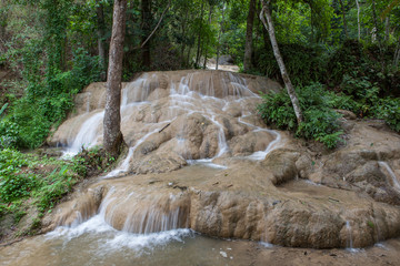 Beautiful sticky waterfall in jungles of Northern Thailand. Blurred white waters of the waterfall flowing down a limestone formations in a tropical green forest.