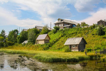 North Russian village Isady. Summer day, Emca river, old cottages on the beach.