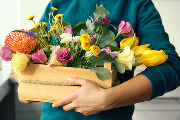 Female florist holding beautiful flower composition in box, closeup