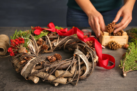 Female hands making decorative wreath in floral shop