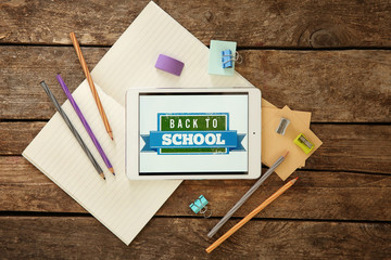 Colourful stationery and tablet with BACK TO SCHOOL phrase on wooden background