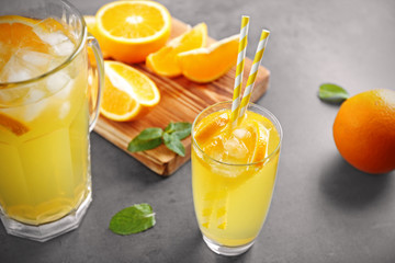 Glass of refreshing orange drink on table