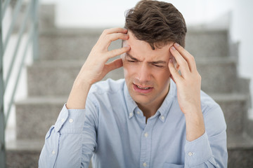 Stressed young businessman suffering from headache