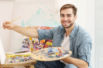 Young male artist painting picture in studio