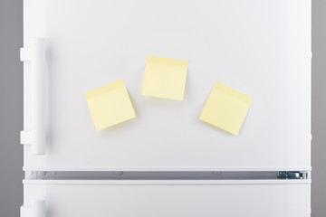Blank light yellow sticky paper notes on white refrigerator