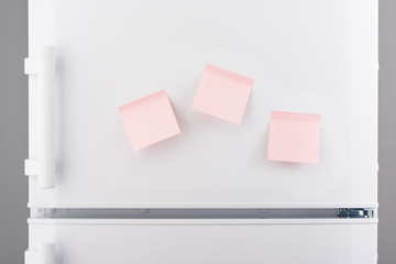 Three blank light pink sticky paper notes on white refrigerator