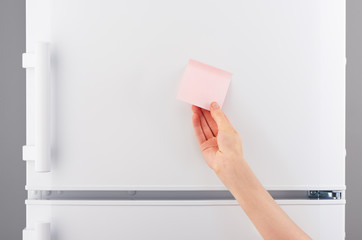 Female hand holding pink paper note on white refrigerator