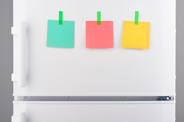 Green, pink, yellow notes attached with stickers on refrigerator