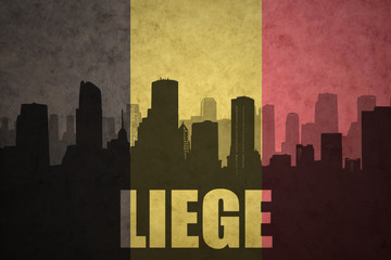 abstract silhouette of the city with text Liege at the vintage belgian flag
