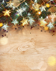 Christmas fir tree with lights of stars on wooden table. Merry Christmas! Top view.