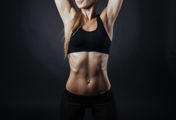 Muscular fitness woman posing on a dark background in studio