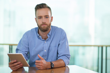 Portrait of serious manager with digital tablet