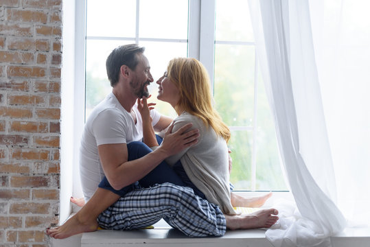 Loving adult couple hugging in bedroom