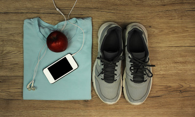 Set for sports: shoes, t-shirt, mobile phone with headphones and red apple close-up on a wooden background, top view