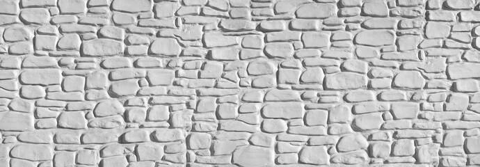 Panorama einer weißen, groben Steinmauer aus gestrichenen Natursteinen