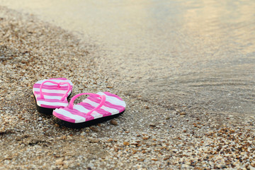 Pair of flip flops on sand beach