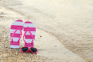 Pink sunglasses with pair of flip flops on the beach sand