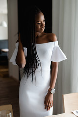 Adorable attractive femine with black skin standing near the table. Girls is wearing elegant white dress with sexy bare shoulders. She looking at the window and put her hand on hair.