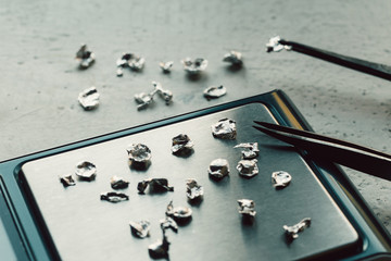 Jewelry tools. Jewellery. Goldsmith workplace, workspace on light background. Hand craft. Workshop. Manufacturing. Weigh-scales with granules of metal silver and platinum. Closeup. Toned