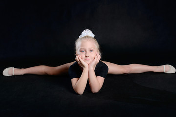 Beautiful sport training girl portrait in leotard in nhe black room. classic portrait of gymnastics girl