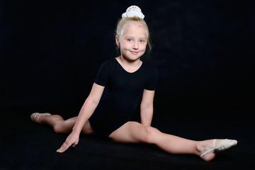 Beautiful sport training girl portrait in leotard in nhe black room. classic portrait of gymnastics girl