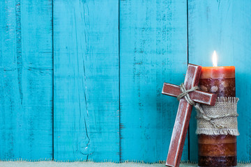 Wooden cross by candle with teal blue wood background