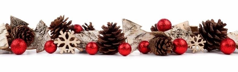 Christmas border with rustic wood tree ornaments, baubles and pine cones isolated on a white background