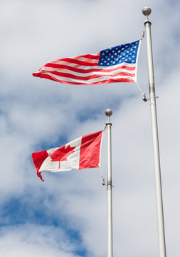 American and Canadian flag on poles hanging on a flag pole in th