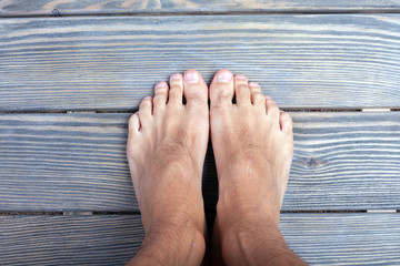 male feet on wooden background.