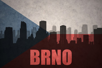 abstract silhouette of the city with text Brno at the vintage czech republic flag