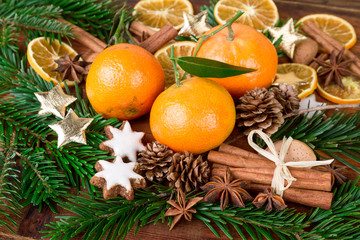 mandarins fruits with fir branch and christmas spices on wooden table