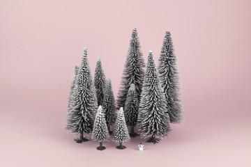 Bodegón mininalista de bosque en invierno con un diminuto muñeco de nieve. Fondo rosa.