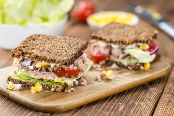 Wooden table with Tuna sandwich (on wholemeal bread; selective f