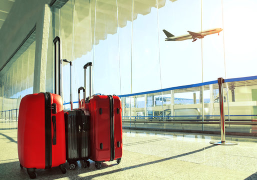stack of traveling luggage in airport terminal and passenger pla