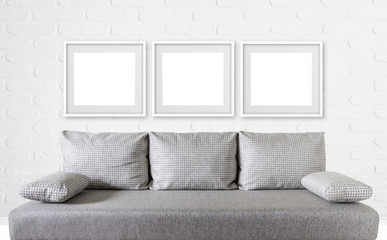 Three blank photo frames over modern couch, against bricks textured wall, interior decor mock up