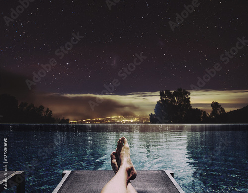 Relaxing In Holidays A Man Feet On Bed At Swimming Pool At Night With City Lights And Stars On