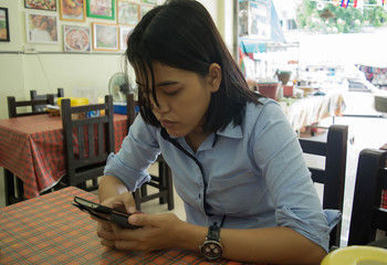 Young Woman Use Smartphone in restaurant