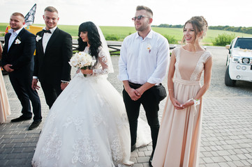 Wedding couple and bridesmaids with best mans background wedding