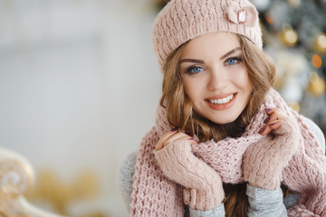 Beautiful young redhead woman with blue eyes and long curly hair,in a beige knitted hat,scarf and gloves posing in Studio on light background ornate Christmas tree with yellow balls